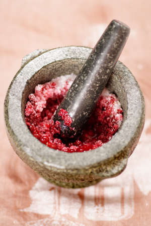 pestel: Cooking salt and redberry marinade in granite mortar, shallow focus