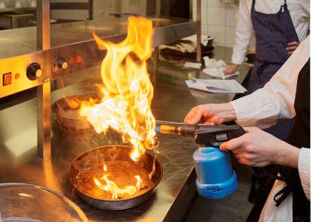 techniek: Chef-kok is het branden aromatische kruiden om een gerecht te roken, commerciële keuken