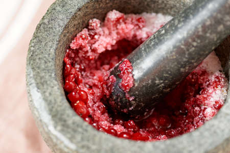 pestel: Salt and redberry marinade in mortar, close-up Stock Photo