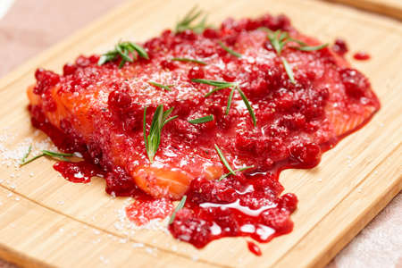 Salmon steak being marinated in salt with redberries and rosemary photo