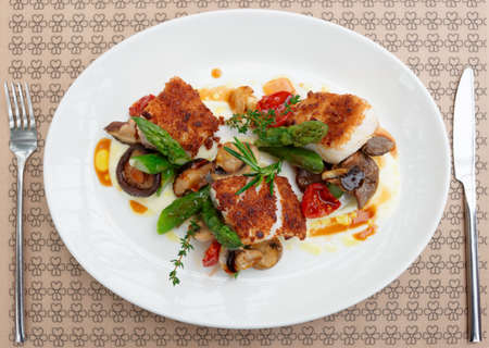 coalfish: Fish fillet with mushrooms and asparagus on restaurant table