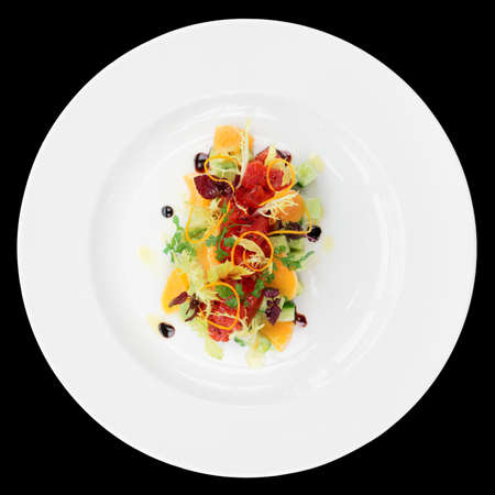 beautiful salad: Tuna tartar with cucumber and orange isolated on black background
