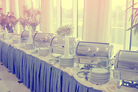 Table with dishware and shiny marmites waiting for guests, toned image photo
