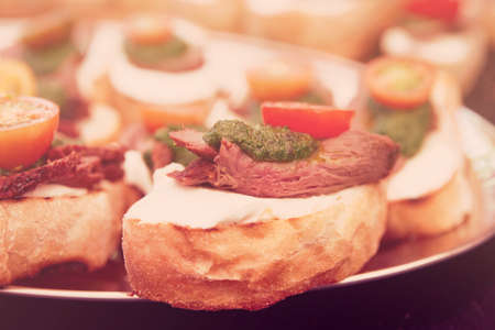 beefsteak: Bruschettas with beefsteak and pesto sauce, close-up, toned image