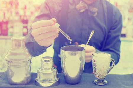 cocteles: Bartender est� haciendo c�ctel en barra de bar, a�adiendo un poco amargo en la coctelera, la imagen en tonos Foto de archivo