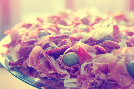cured ham: Platter with spanish cured ham on table, toned image