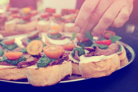 haciendo pan: Chef est� haciendo bruschettas con bistec y salsa de pesto, imagen de tonos