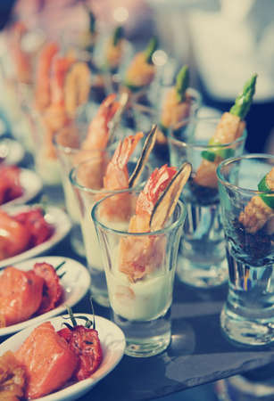 canapes: Glasses with seafood snacks -  banquet dish, toned image Stock Photo