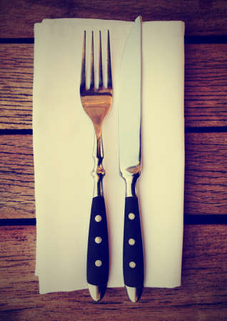 Fork, knife and napkin on wooden restaurant table, toned image photo