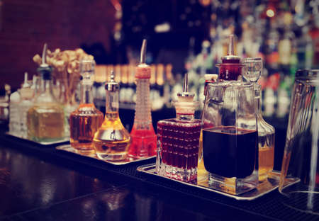 bar counter: Bitters and infusions on bar counter, bar bottles in blurred background, toned image