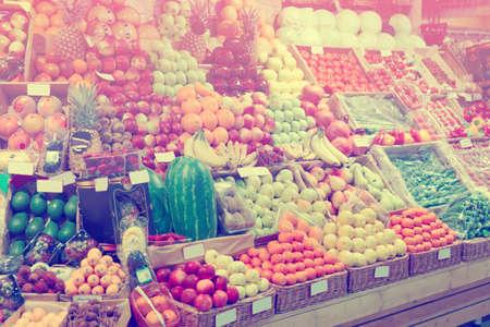 Plank met vruchten op een boerderij markt, merken wazig of verwijderd, getinte afbeelding