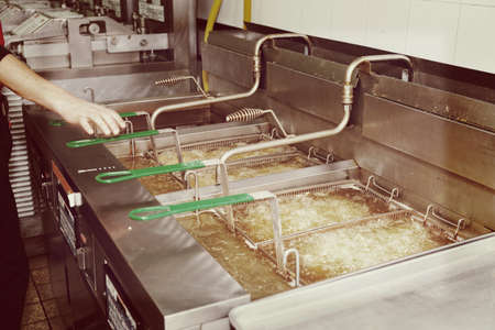 fryer: Deep fryers with boiling oil on fast food kitchen, toned picture