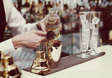 Bartender is pouring liquor in golden shaker, toned image 스톡 콘텐츠