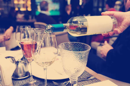 hand holding bottle: Waiting is pouring white wine in restaurant, toned image Stock Photo