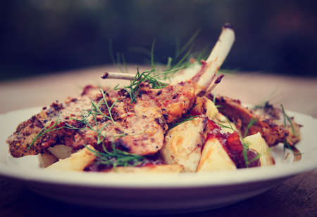 the lamb: Grilled rack of lamb with fried potatoes and onion chutnee shot outdoors, toned image