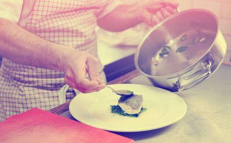 seabass: Chef est� sirviendo lubina al vapor con espinacas, imagen de tonos