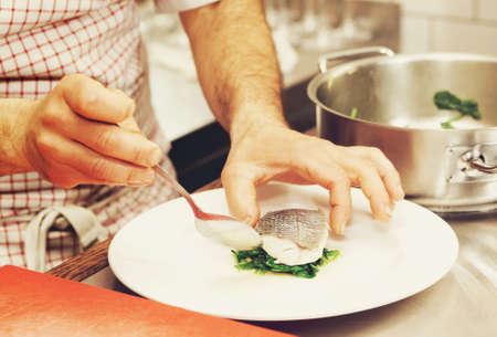 seabass: Chef is serving steamed seabass with spinach, toned image Stock Photo