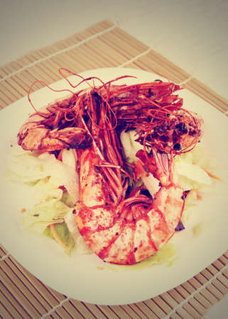 seared: Seared Jumbo prawns with lettuce on restaurant table, toned image Stock Photo