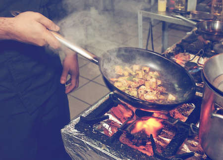 gas stove: Chef is cooking seafood dish - stir fry method, toned image