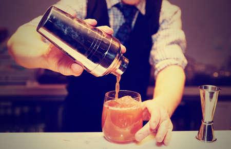 Bartender macht Cocktail an Bartheke, getönte Bild