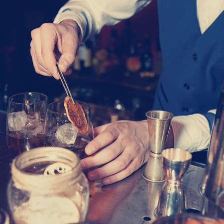 Barman works at bar counter, blue toned image