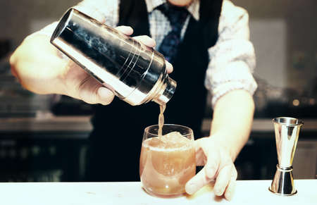 pour: Bartender is making cocktail at bar counter Stock Photo