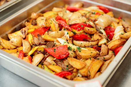 wedges: Steel container with roasted potato wedges and vegetables
