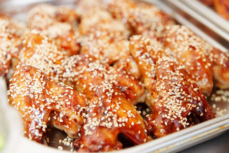 sweet and savoury: Grilled chicken wings with sesame in stainless steel container