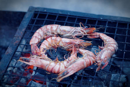 blue  toned: Shrimps on charcoal grill, outdoor picnic, blue toned image Stock Photo