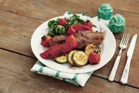 New York steak with vegetables shot outdoor, toned image photo