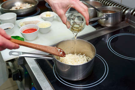 Chef is adding white wine to risotto, copy space