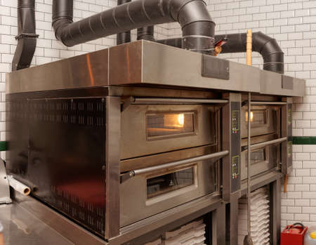 oven: Large industrial pizza oven in restaurant