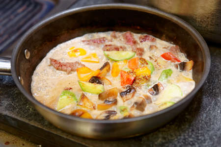 broiling: Meat and vegetables being cooked in cream Stock Photo