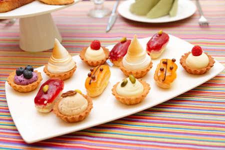 postre: Conjunto de pequeñas tortas en la placa, primer plano Foto de archivo