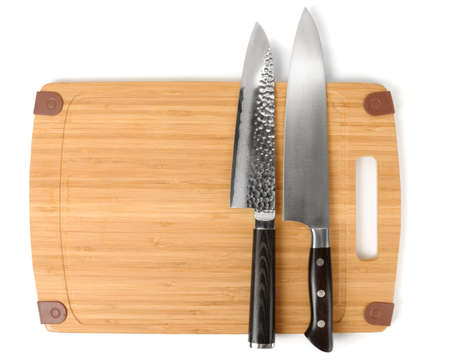 welded: Two knives on a bamboo cutting board, isolated on white