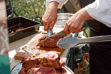 barbecue: Chef is cutting meat, toned image