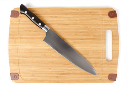 grinded: Chefs knife on a cutting board isolated over white