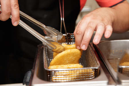 friture: Chef is cooking chicken nuggets in a deep fryer