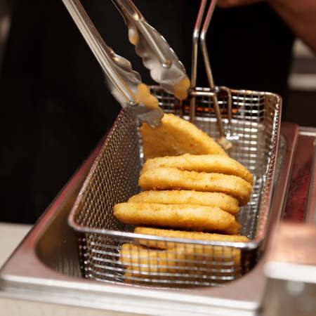 friture: Chef is cooking nuggets in a deep fryer