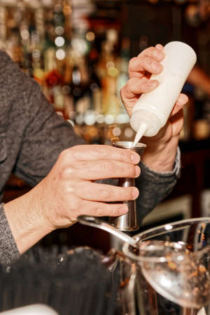 adding: Bartender is adding secret ingredient in a cocktail