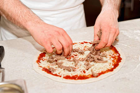 pizza maker: Making of a meat pizza, professional kitchen