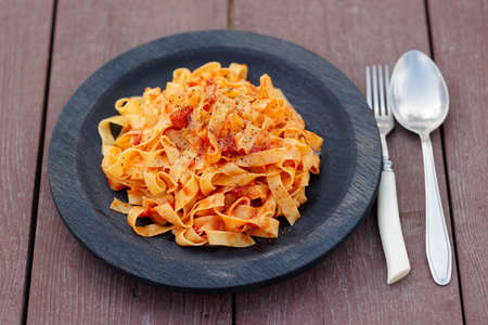 outdoor shot: Tagliatelle with tomato sauce in wooden plate, outdoor shot