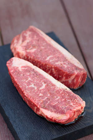 two pieces: Two pieces of raw striploin steak on wooden plank