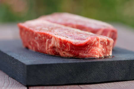 two pieces: Two pieces of raw striploin steak, outdoor shot Stock Photo