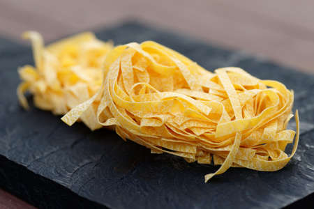 black boards: Egg tagliatelle on wooden plank, limited focus depth