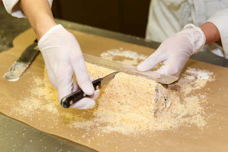 food safety: Female pastry chef is portioning the biscuit cake Stock Photo