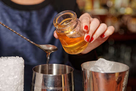 nail bar: Bartender is adding honey to the mixing glass Stock Photo