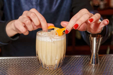 nail bar: Female bartender is adding orange zest to cocktail