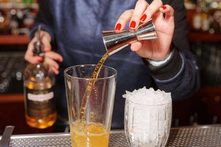 botella de whisky: barman femenino es la adición de whisky al vaso mezclador
