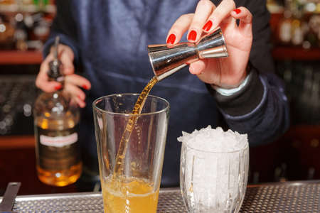 bartender: Female bartender is adding whisky to the mixing glass Stock Photo